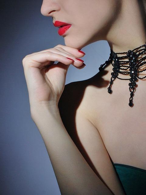 赤い唇と黒のデザインネックレスが格調高い女性