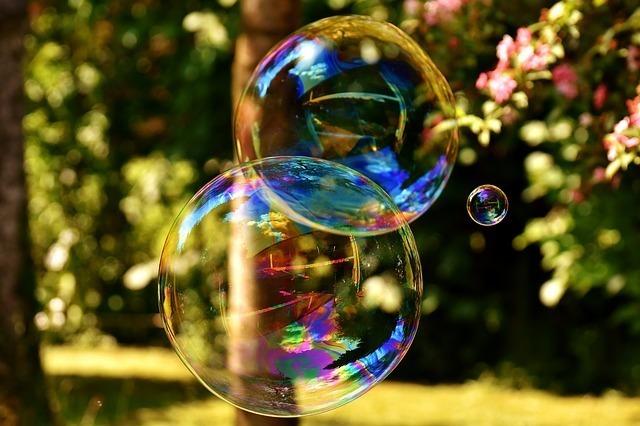 大きなシャボン玉2個と小さなシャボン玉1個が宙を舞っている画像