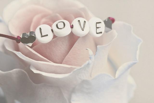 淡いピンクのバラにLOVEの文字のアクセサリーがかけられた画像