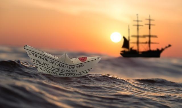 夕日が照らす海に浮かぶ英字新聞の船