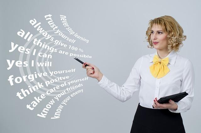 黄色リボンネクタイの女性があらゆる目標値を英語で確認している画像