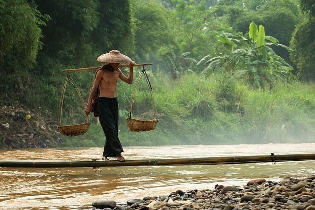 天秤棒を担いで川を渡るアジアの人