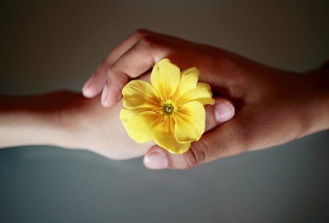 花を持つ手が重なり合っている