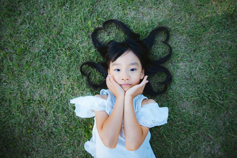 芝生に寝転んでいる女の子。髪でハートを形作っている