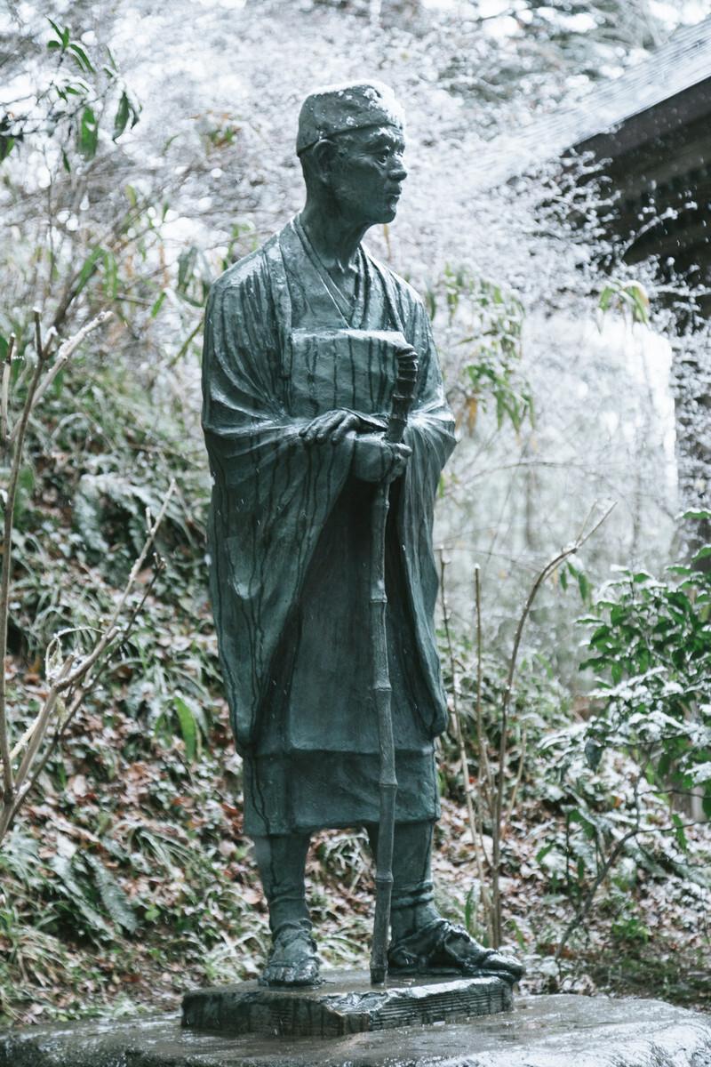 雪の中にたたずむ松尾芭蕉の像