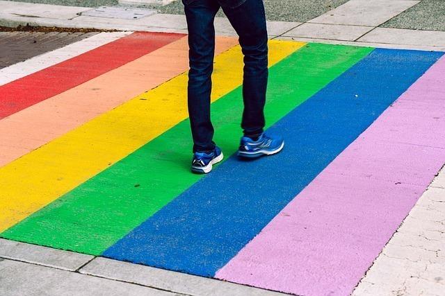 虹色の横断歩道を渡る男性