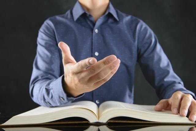 本を開きながら説明する男性