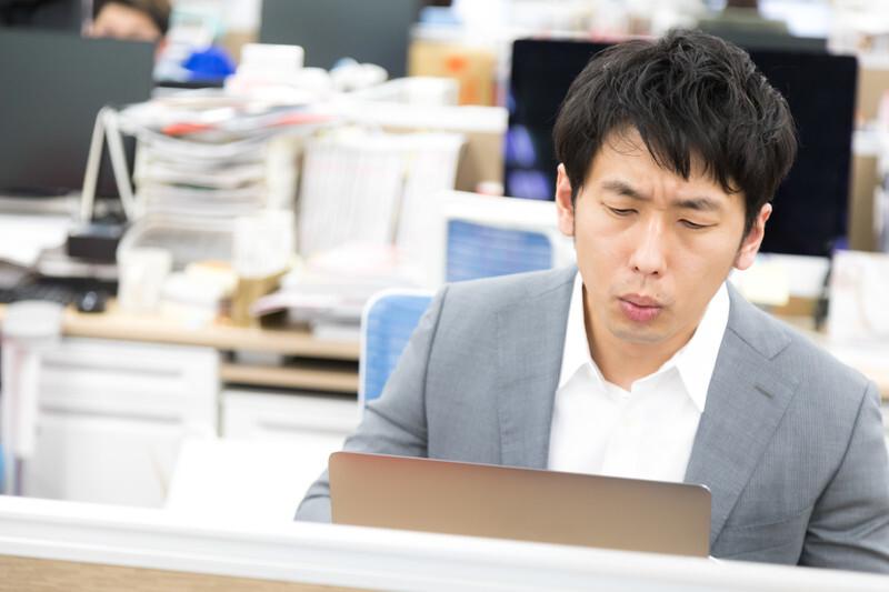 顔をしかめながら仕事する男性