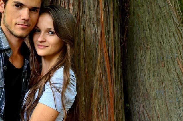 木に寄りかかるこちらを見るカップル