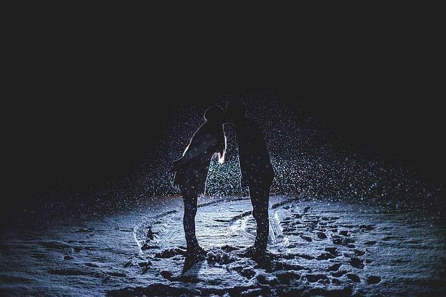 暗い雪の上でキスするカップル