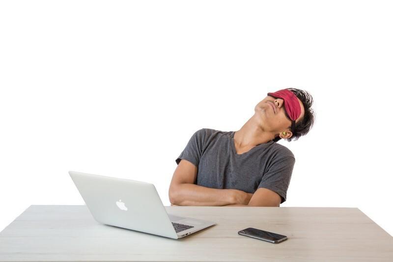 パソコンの前で寝る男性