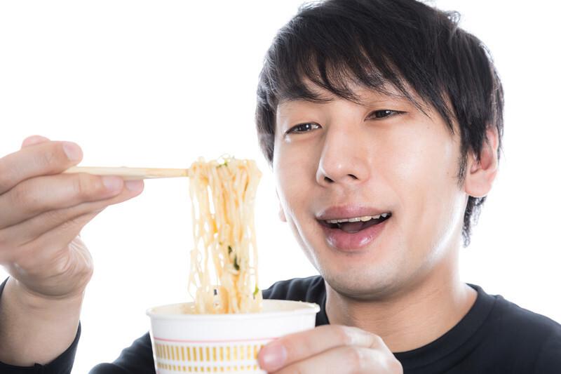 カップラーメンを食べる男性