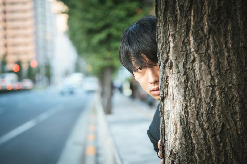 木に隠れる男性