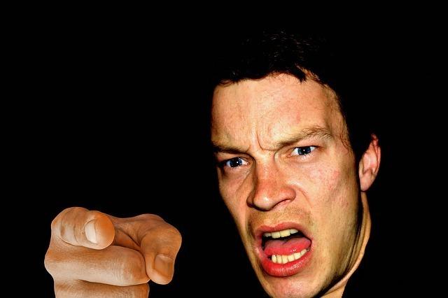 指をさして怒る男性