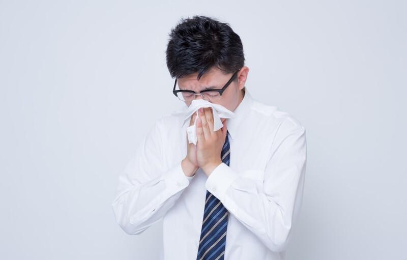 鼻をかんでいる男性