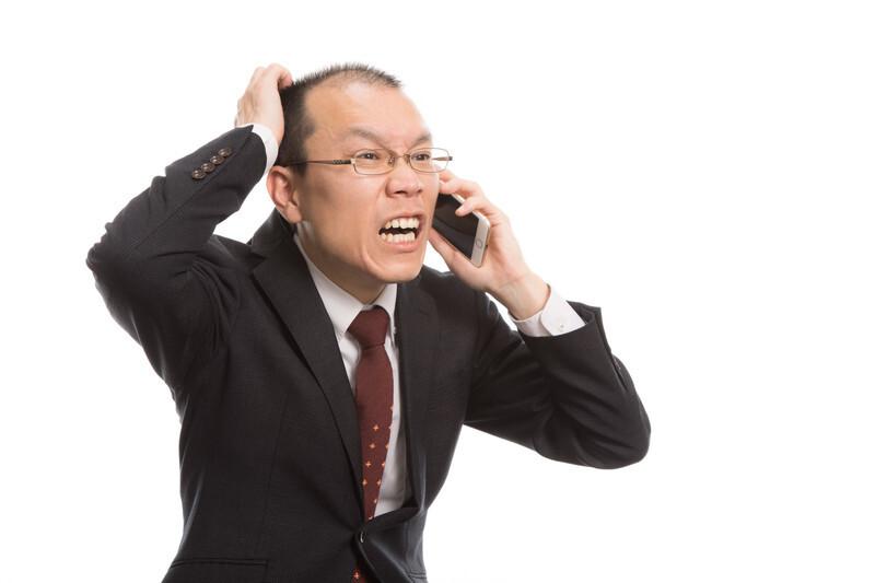 電話しながら苦しい表情をする男性